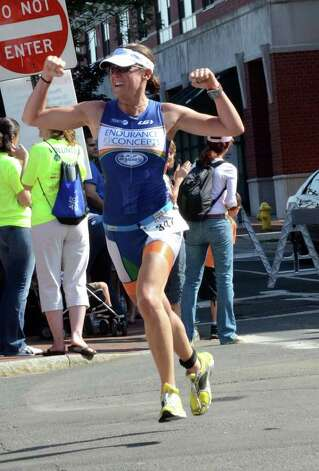 First place female finisher Brigitte Paulick, of New York, cheers as she approaches the finish line during the Stamford KIC IT Triathlon in Columbus Park Sunday June 27, 2010. The race features a mile swim off of Cummings Beach followed by a 24.8 mile bike throughout the city and a 6 mile run finishing at Columbus Park. The event drew more than 500 athletes raising money for Greenwich based Kids in Crisis. Photo: Amy Mortensen / Connecticut Post Freelance