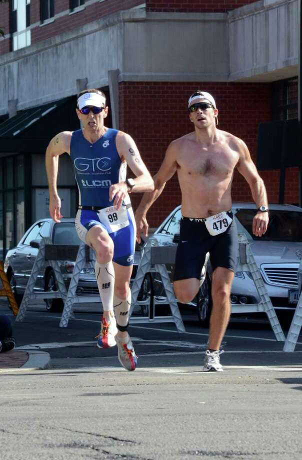 George Bouloukos, of Stamford and Brendan McEwan, of New Canaan compete in the Stamford KIC IT Triathlon in Columbus Park Sunday June 27, 2010. The race features a mile swim off of Cummings Beach followed by a 24.8 mile bike throughout the city and a 6 mile run finishing at Columbus Park. The event drew more than 500 athletes raising money for Greenwich based Kids in Crisis. Photo: Amy Mortensen / Connecticut Post Freelance