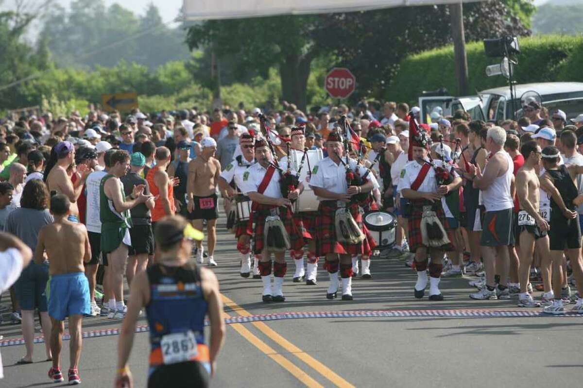 The Connecticut Firefighters Pipes and Drums band makes their way through the runners before the start of the Stratton Faxon Fairfield Half Marathon on Sunday, June 26, 2011.