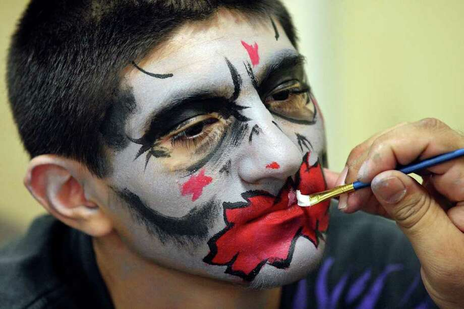 Brandon Rodriguez, 12, has his face painted by Sergio Guerra, 32, during the Texas Comicon 2011 Sunday, June 26, 2011, at the San Antonio Event Center. Photo: PHOTO BY EDWARD A. ORNELAS/eaornelas@express-news.net / © SAN ANTONIO EXPRESS-NEWS (NFS)