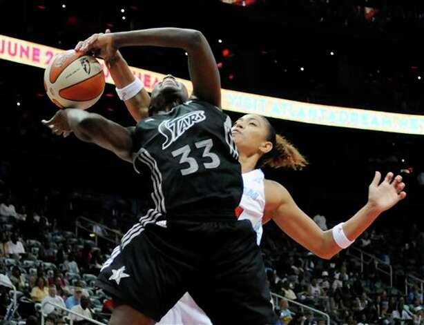 Silver Stars forward Sophia Young, front, is fouled by Atlanta Dream center Erika de Souza during the second half  Sunday in Atlanta. San Antonio won 92-86. (AP Photo/Tami Chappell) Photo: Tami Chappell, Associated Press / Kevin Liles