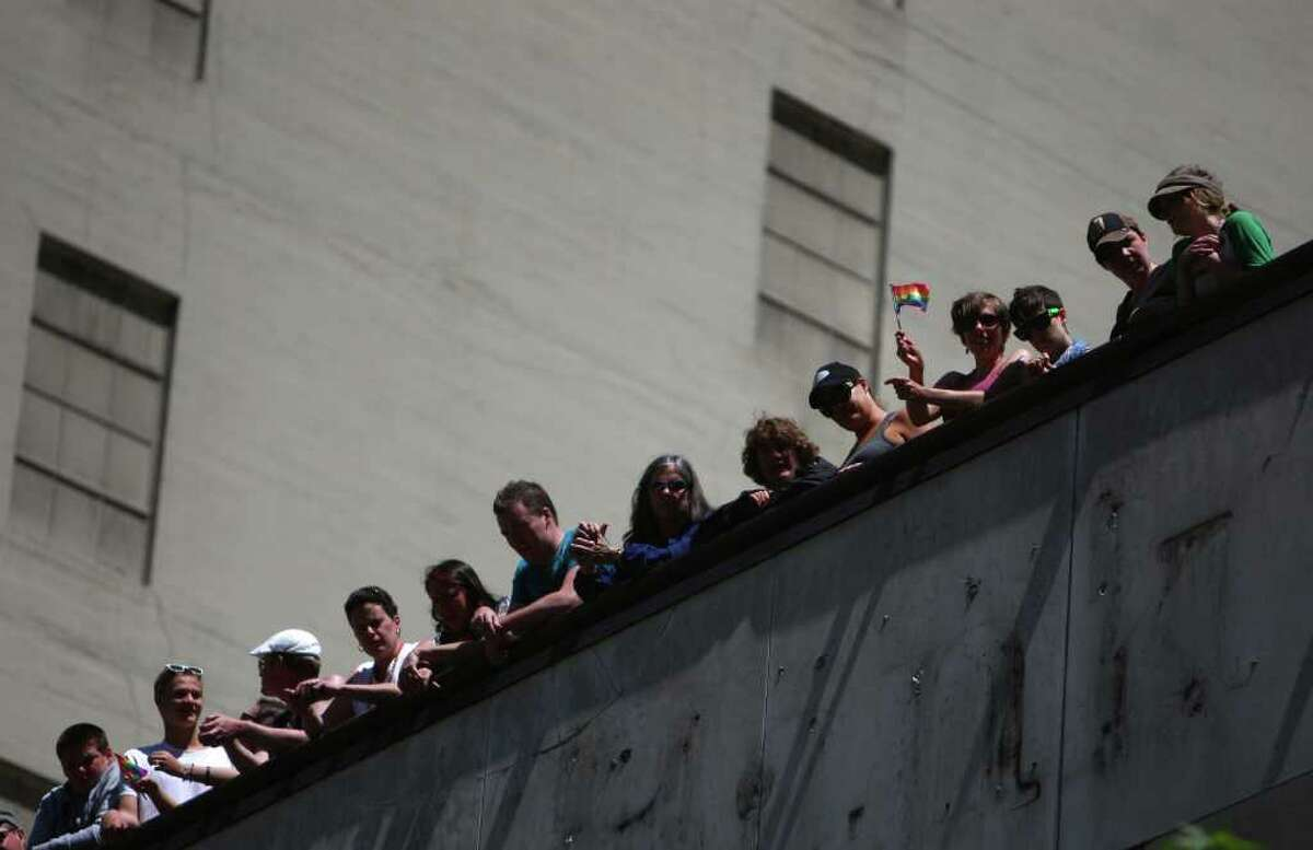Spectators watch from the roof of a building during the 2011 Seattle Pride Parade.