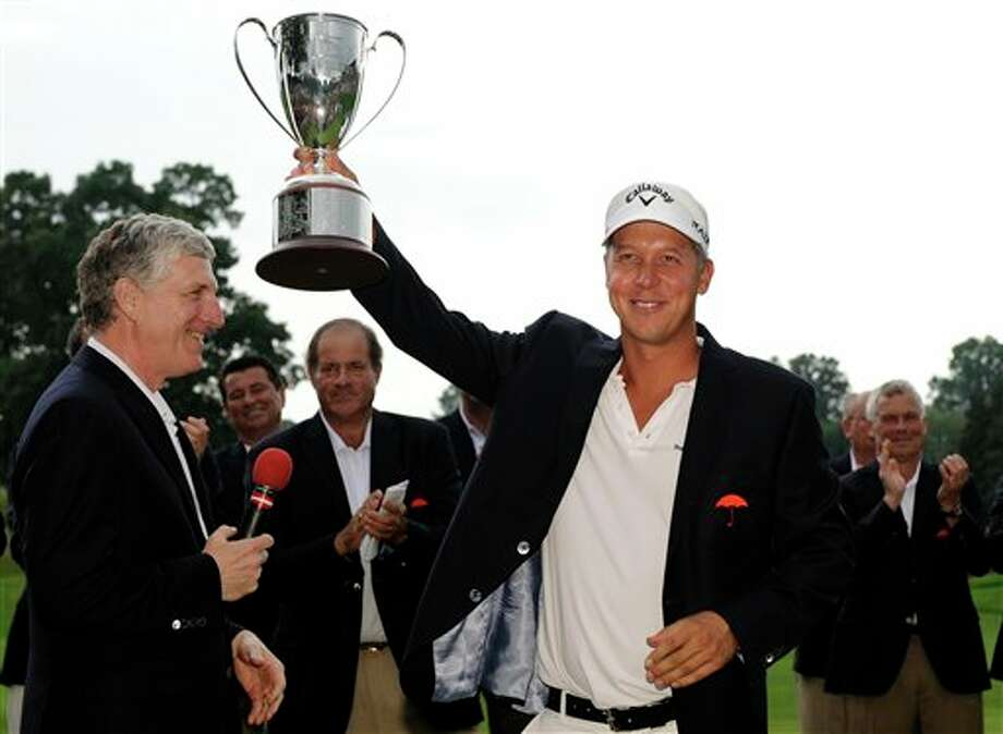 Frederik Jacobson, of Sweden, receives his championship trophy from Travelers chief executive Jay Fishman, left, after winning the Travelers Championship golf tournament in Cromwell, Conn., on Sunday, June 26, 2011. Jacobson's 20-under par victory was his first on the PGA tour. (AP Photo/Fred Beckham) Photo: AP