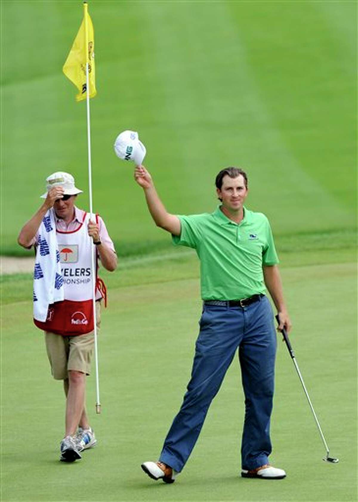 Michael Thompson, right, acknowledges the gallery after making a birdie on the 18th hole during the final round of the Travelers Championship golf tournament in Cromwell, Conn., on Sunday, June 26, 2011. Thompson finsihed the final round with an 18-under par 262. (AP Photo/Fred Beckham)