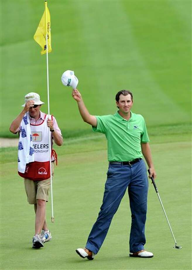 Michael Thompson, right, acknowledges the gallery after making a birdie on the 18th hole during the final round of the Travelers Championship golf tournament in Cromwell, Conn., on Sunday, June 26, 2011. Thompson finsihed the final round with an 18-under par 262. (AP Photo/Fred Beckham) Photo: AP