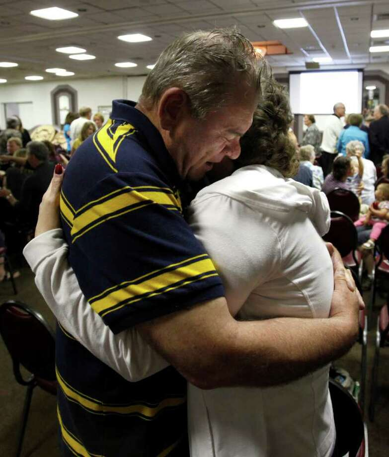 John and Deb Walker, evacuated from their home flooded by the Souris River, hug and pray during a church service for three Lutheran congregations held at The Vegas Hotel Sunday, June 26, 2011 in Minot, N.D. (AP Photo/Charles Rex Arbogast) Photo: Charles Rex Arbogast
