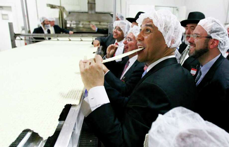 Newark Mayor Cory Booker eats a piece of a large matzo that was baked during the grand opening of the headquarters for the Manischewitz company, on June 14, 2011, in Newark, N.J. The kosher product company claims the matzo is the world's largest. Photo: Julio Cortez/Associated Press