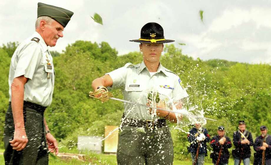 Kiara Esperanza slices open a champange bottle with a sabre under the direction of Col. Peter Moritz during trooper graduation ceremonies of the Second Company Governor's Horse Guard, in Newtown, Sunday, June 26, 2011. Photo: Michael Duffy / The News-Times