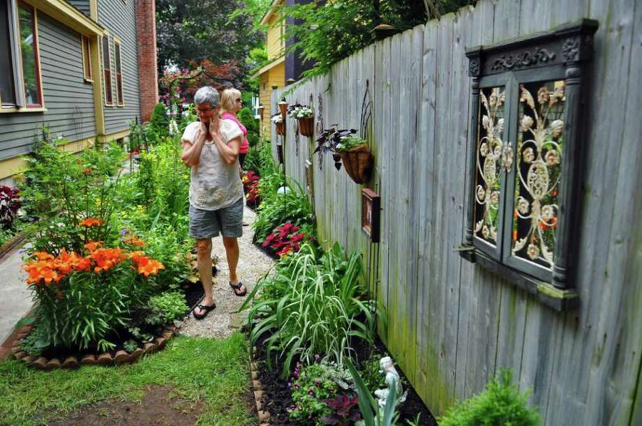 Cynthia Byers of Voorheesville, left, and Kathy Ashline of Guilderland, right, tour the garden of Mona and Christopher Newbert during the Secret Gardens Tour, run by Soroptimist International, on Sunday  June 26, 2011 in Saratoga Springs, NY.  ( Philip Kamrass / Times Union) Photo: Philip Kamrass