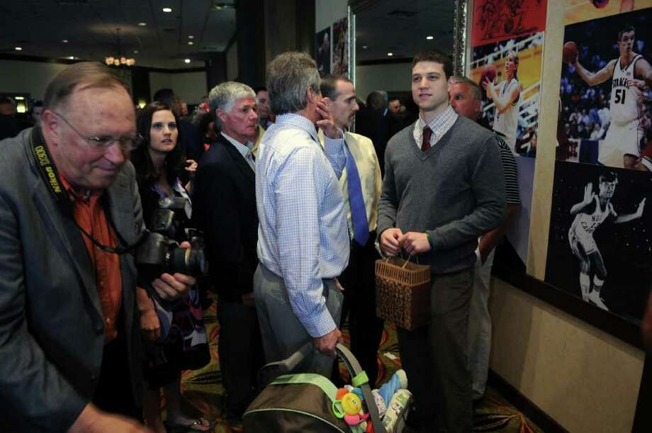 NBA first round draft pick Jimmer Fredette, a Glens Falls High School graduate, is surrounded by  family and friends and well wishers after arriving at the Capital District Hall of Fame dinner at the Crowne Plaza on Sunday evening June 26, 2011 in Albany, NY. His father Al stands next to him  at left. ( Philip Kamrass / Times Union) Photo: Philip Kamrass
