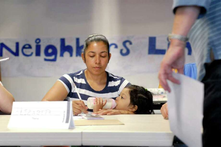 Elizabeth Palma works on her English while holding her daughter Katherine at Neighbors Link Stamford is a new non-profit organization that provides a comprehensive resource center for recent immigrants in the Stamford, Connecticut area on Monday June 27, 2011. Photo: Dru Nadler / Stamford Advocate Freelance