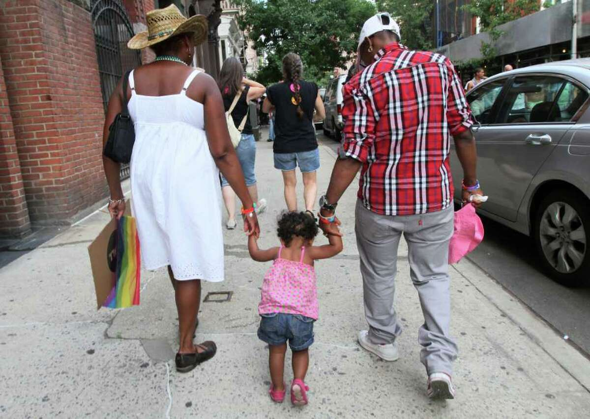 Everine Hill, left, and her partner Carshella Hewie, right, walk with their 17 month old daughter Nasya Hewie-Hill after marching in the Gay Pride Parade Sunday June 26, 2011 in New York. Hill and Hewie have been together for 13 years.