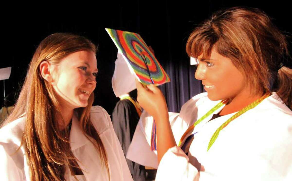 Danbury High School graduate Megan Ayre shows the artwork on her cap to fellow grad Naomi Alphonso just before the start of commencement exercises Monday, June 27, 2011.