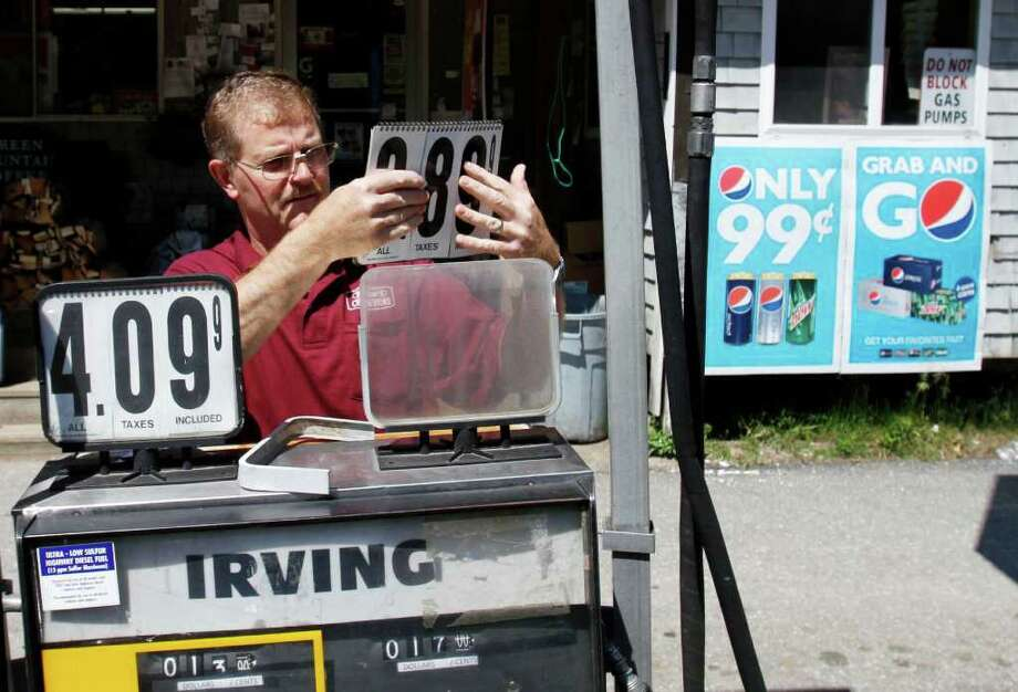 Convenience story owner Floyd Bisson, lowers the price of regular gas at the pumps in front of his store in Phippsburg, Maine on  Monday, June 27, 2011. The nationwide average for retail gasoline fell to $3.57 per gallon Monday according to AAA, Wright Express and the Oil Price Information Service. Prices have dropped 24 cents in a month. (AP Photo/Pat Wellenbach) Photo: Pat Wellenbach