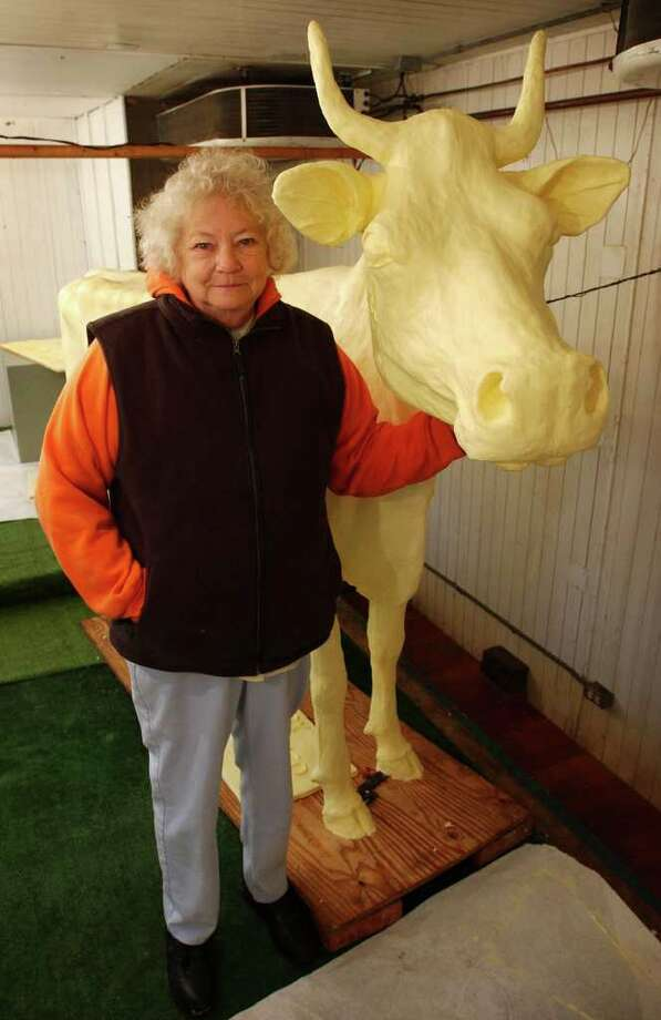 "FILE - In this Aug. 6, 2003, file photo Norma ""Duffy"" Lyon stands next to a life-size dairy cow she sculpted from butter at the Iowa State Fair in Des Moines, Iowa.  Lyon, who famously sculpted butter into cows, Elvis and even Jesus for the Iowa State Fair, has died. She was 81. (AP Photo/Charlie Neibergall, File) Photo: CHARLIE NEIBERGALL"