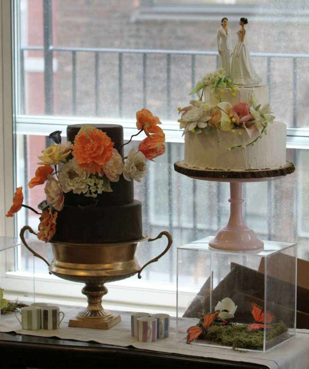 An almond cake with New York City rooftop honey buttercream icing, right, and a chocolate cake with chocolate gnash icing are on display at the Sugar Flower Cake Shop, Monday, June 27, 2011 in New York. (AP Photo/Mary Altaffer)