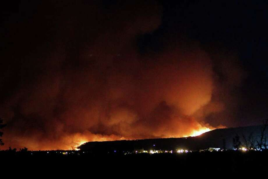 A wildfire crests over the hills above Los Alamos National Labs Sunday June 26, 2011 in New Mexico.  A fast-moving wildfire forced officials at the Los Alamos National Laboratory to close the site Monday.  (AP Photo/Luis Sanchez Saturno/The New Mexican) Photo: LUIS SANCHEZ SATURNO