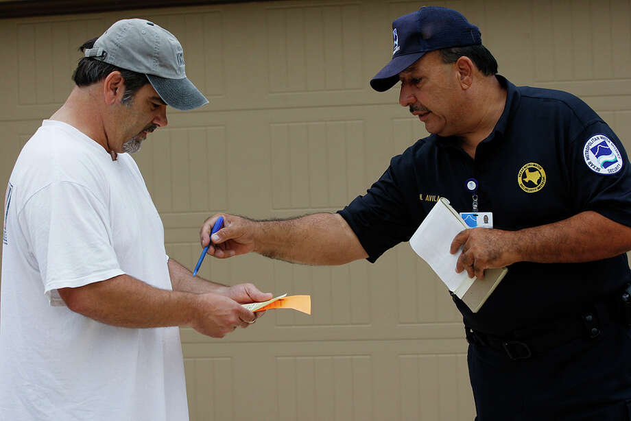 BexarMet Water District Security Officer Henry Avila hands out a warning to Stephen Faulisi for watering on a wrong day, on June 21, 2011. Fausili explained that he was figuring out his sprinkler system and forgot to turn if off after watering on Monday, his assigned day. Avila was patrolling the far west Bexar County area. Photo: Jerry Lara / glara@express-news.net