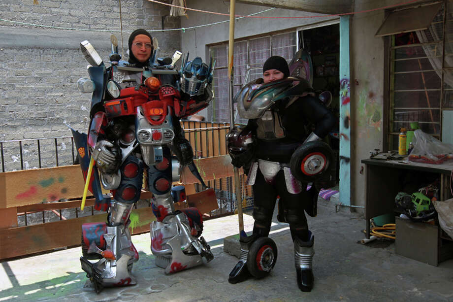 Jose Luis Mendez Luna, 38, and his wife Jessica Legorreta, 29, pose wearing their Optimus Prime and RC Transformer costumes at their home in a working class neighborhood in Mexico City, Wednesday, June 8, 2011. Luna whose daytime job is a plumber, is, along with his wife, both avid cosplayer and cosmakers, a type of performance art in which participants don and make costumes and accessories to represent a specific character. Their characters of choice are the Transformers and the Star Wars characters. Photo: Christian Palma, AP Photo/Christian Palma / AP
