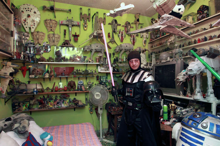 Jose Luis Mendez Luna, 38, poses wearing his Darth Vader costume inside his bedroom at home in a working class neighborhood in Mexico City, Wednesday, June 8, 2011. Luna whose daytime job is a plumber, is, along with his wife, an avid cosplayer and cosmaker, a type of performance art in which participants don and make costumes and accessories to represent a specific character. Their characters of choice are the Transformers and the Star Wars characters. Photo: Christian Palma, AP Photo/Christian Palma / AP