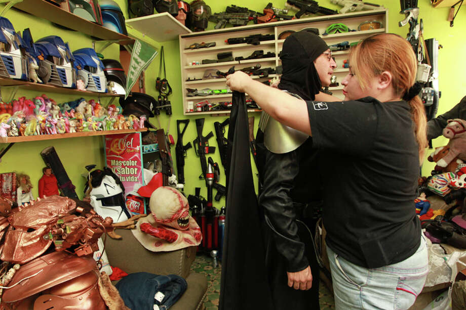 Jose Luis Mendez Luna, 38, gets help from his wife, Jessica Legorreta, 29, as he prepares to dress as Darth Vader at his home in a working class neighborhood in Mexico City, Wednesday, June 8, 2011. Luna whose daytime job is a plumber, is, along with his wife, an avid cosplayer and cosmaker, a type of performance art in which participants don and make costumes and accessories to represent a specific character. Their characters of choice are the Transformers and the Star Wars characters. Photo: Christian Palma, AP Photo/Christian Palma / AP
