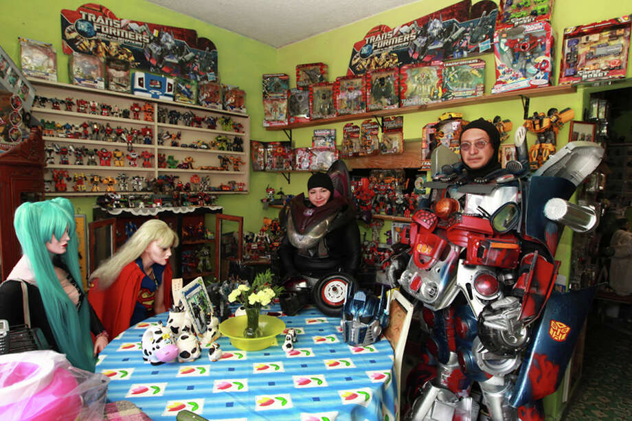 Jose Luis Mendez Luna, 38, and his wife Jessica Legorreta, 29, pose with their Optimus Prime and RC Transformer costumes in their dining room at a working class neighborhood in Mexico City, Wednesday,June 8, 2011. Luna whose daytime job is a plumber, is, along with his wife, an avid cosplayer and cosmaker, a type of performance art in which participants don and make costumes and accessories to represent a specific character. Their characters of choice are the Transformers and the Star Wars characters. Photo: Christian Palma, AP Photo/Christian Palma / AP