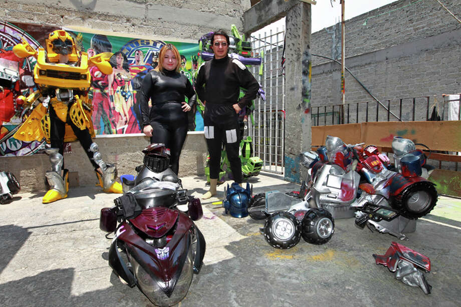 "Jose Luis Mendez Luna, 38, right, and his wife Jessica Legorreta, 29, pose after wearing their Optimus Prime and RC Transformer costumes at their home in a working class neighborhood in Mexico City, Wednesday, June 8, 2011. Luna whose daytime job is a plumber, is, along with his wife, both avid cosplayer and cosmakers, a type of performance art in which participants don and make costumes and accessories to represent a specific character. Their characters of choice are the Transformers and the Star Wars characters. The character at left is known as ""Bumblebee"". Photo: Christian Palma, AP Photo/Christian Palma / AP"