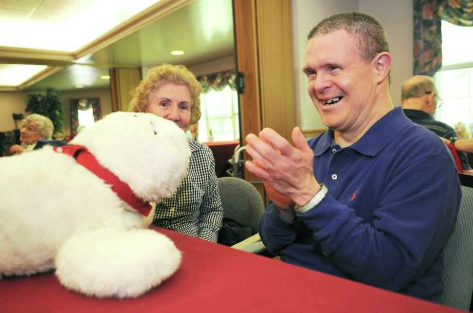 Arnoldo Castillo claps for Paro the baby seal robot while his sister Maria Delpino watches as they sit in Greenwich Woods' specialty care unit for the the Alzhheimer's and the memory impaired, on Wednesday, May 25, 2011. Photo: Helen Neafsey / Greenwich Time
