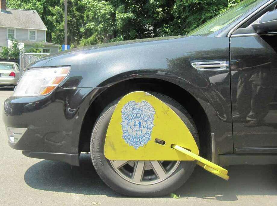 "Pictured is a detective's vehicle in the Fairfield Police Department parking lot that has been ""booted"" for demonstrative purposes. The Fairfield Police Department recently reinstituted the Boot Program to force collection of hundreds of dollars in unpaid parking tickets. Once a vehicle has been booted, it is immobilized until the owner pays all of his or her fines. Photo: Kirk Lang / Fairfield Citizen"