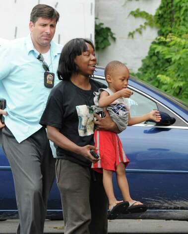 Chante Coleman is all smiles Tuesday as she carries her son, Dymere A. Johnson, 3, into the Albany Police Department's Center Station.  With them is Detective Andy Tarkanian of the Juvenile Division.  The boy vanished for several hours Tuesday morning.  (Skip Dickstein / Times Union) Photo: SKIP DICKSTEIN