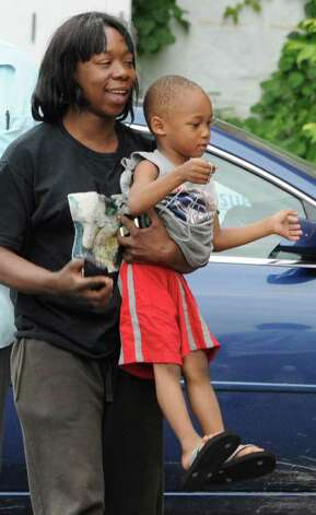 Chante Coleman is all smiles Tuesday as she carries her son Dymere A. Johnson to the Albany Police Department's Center Station. (Skip Dickstein / Times Union) Photo: SKIP DICKSTEIN