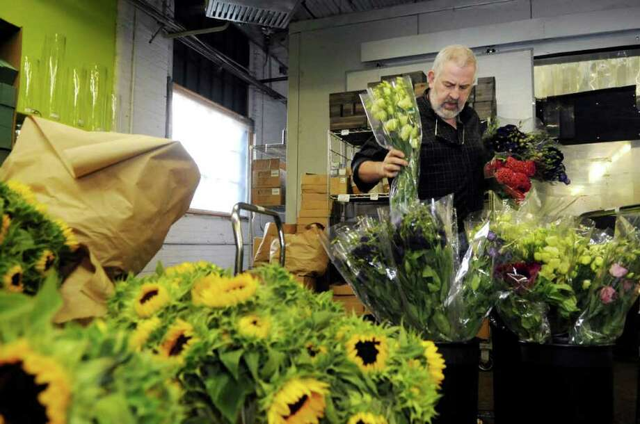 Gary Zinsmeyer, a Stamford florist and event planner, looks at flowers at East Coast Wholesale Florist in Norwalk on Tuesday, June 28, 2011. Zinsmeyer has provided flowers for a number of same-sex weddings in Connecticut. Photo: Helen Neafsey / Greenwich Time