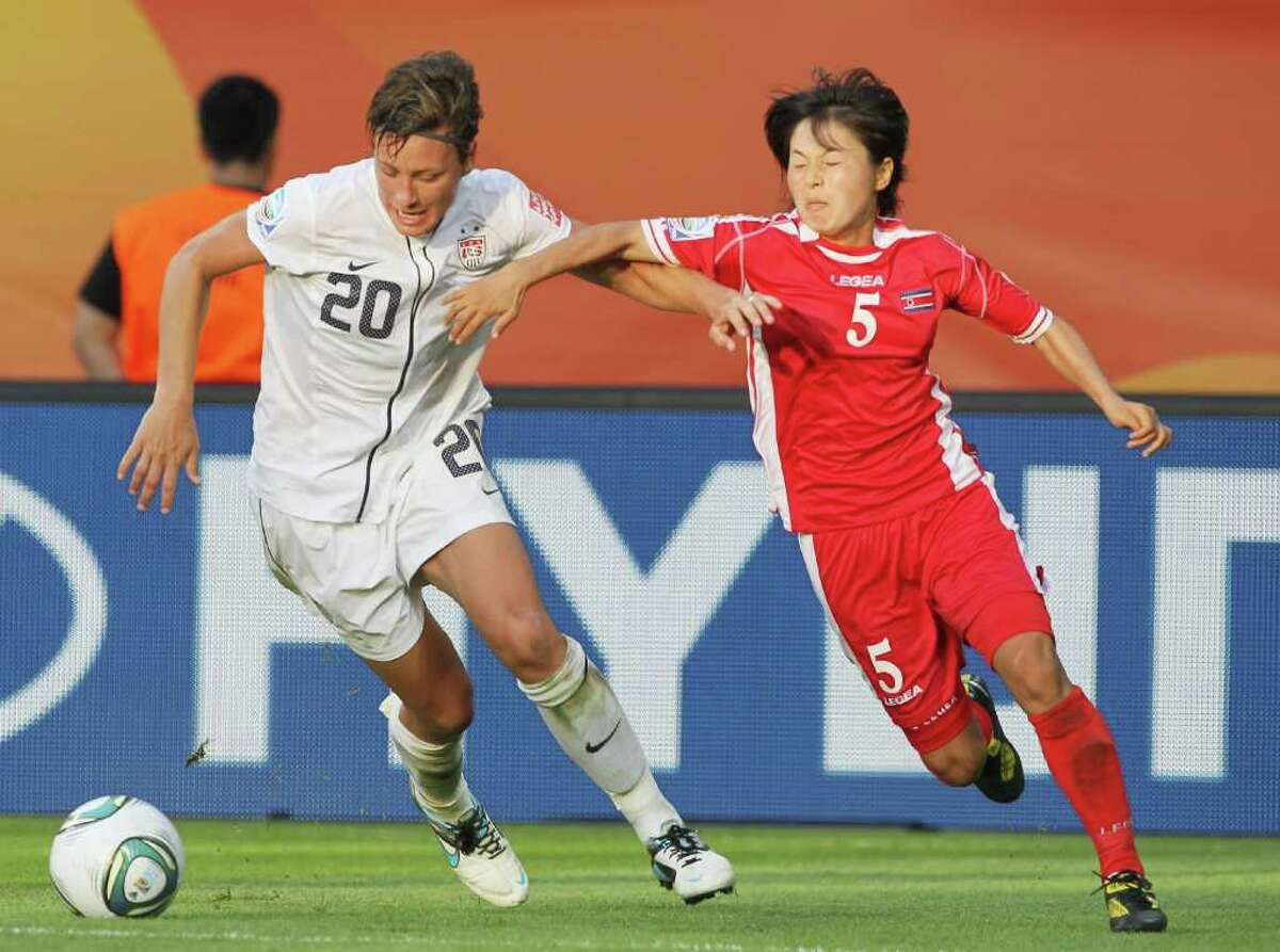 Abby Wambach of the U.S. (left) battles for the ball with Jong Sun Song of North Korea during the FIFA Women's World Cup Group C match between USA and Korea at Rudolf-Harbig-Stadion on June 28, 2011 in Dresden, Germany.