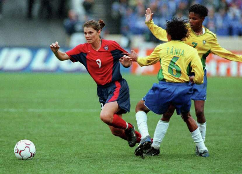 U.S. Women's National Team player Mia Hamm (left) dribbles past Brazilian players Tania (center) and