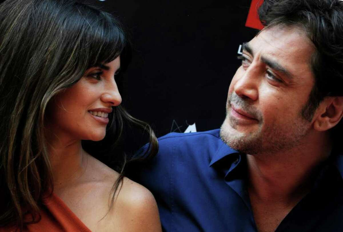 Spanish actress Penelope Cruz talks with her husband Spanish actor Javier Bardem during the opening of the