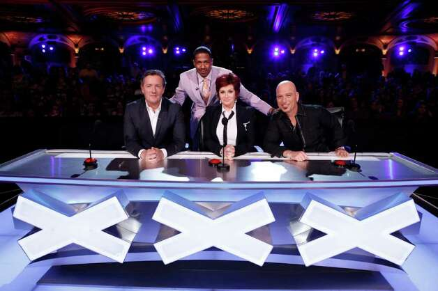 """America's Got Talent"" judges Piers Morgan, Sharon Osbourne and Howie Mandel, and host Nick Cannon (standing)"