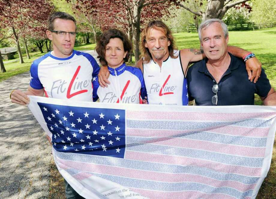 From left, Markus Schuh, Andrea Schmidt, Achim Heukemes and John Michelotti hold a flag commemorating the Sept. 11, 2001,  attacks at the upper Riversville Road home of Schuh on May 5, 2011. Schuh and Schimdt will be acting as support staff for Heukemes who is planning to cross the American continent twice starting on June 25 by biking to San Diego and then by running back, finishing his race at Ground Zero on Sept. 11, 2011, to commemorate the 10th anniversary of the terrorist attacks. Michelotti is the founder of the Flag of Honor/Flag of Heros Project, donating framed American flags with the names of the victims of the Sept. 11 terrorist attacks to the next of kin of the victims. Photo: File Photo / Greenwich Time File Photo
