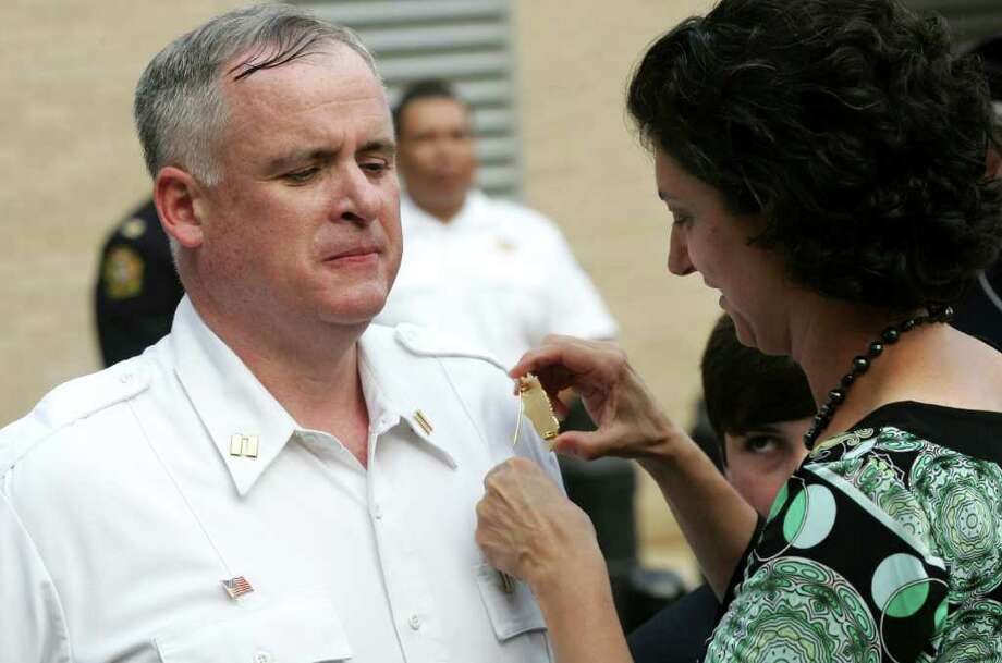 Newly appointed deputy chief fo the Greenwich Police Department, James Heavey, stands as his wife, Kia, pins his new badge to his shirt during a ceremony in front fo Greenwich police headquarters Tuesday evening, June 28, 2011. Photo: David Ames, David Ames/For Greenwich Time / Greenwich Time Freelance