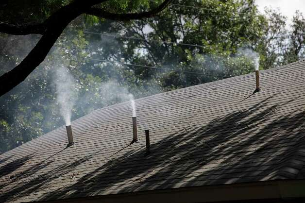Smoke billows from residential vent pipes as SAWS conducts a smoke test on sewer lines along Rocky Oak Street in the city's North Central Side. Photo: JERRY LARA / SAN ANTONIO EXPRESS-NEWS