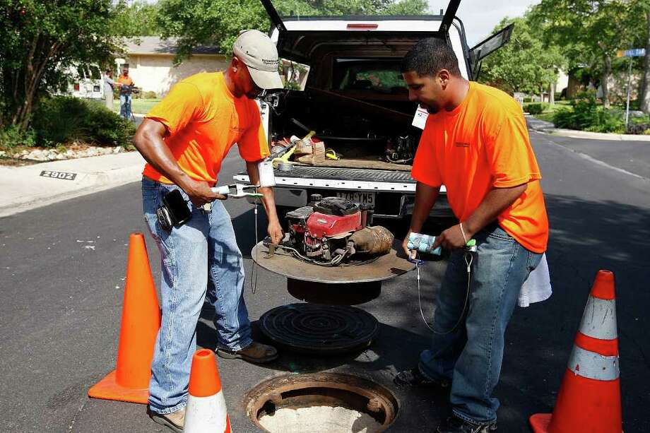 SAWS contract worker Cameron Smith (left) and Alfredo Mata set up a blower fan as they get ready to conduct a smoke test on sewer lines along Rocky Oak Street in the city's North Central Side. Photo: JERRY LARA, Jerry Lara / Glara@express-news.net / SAN ANTONIO EXPRESS-NEWS