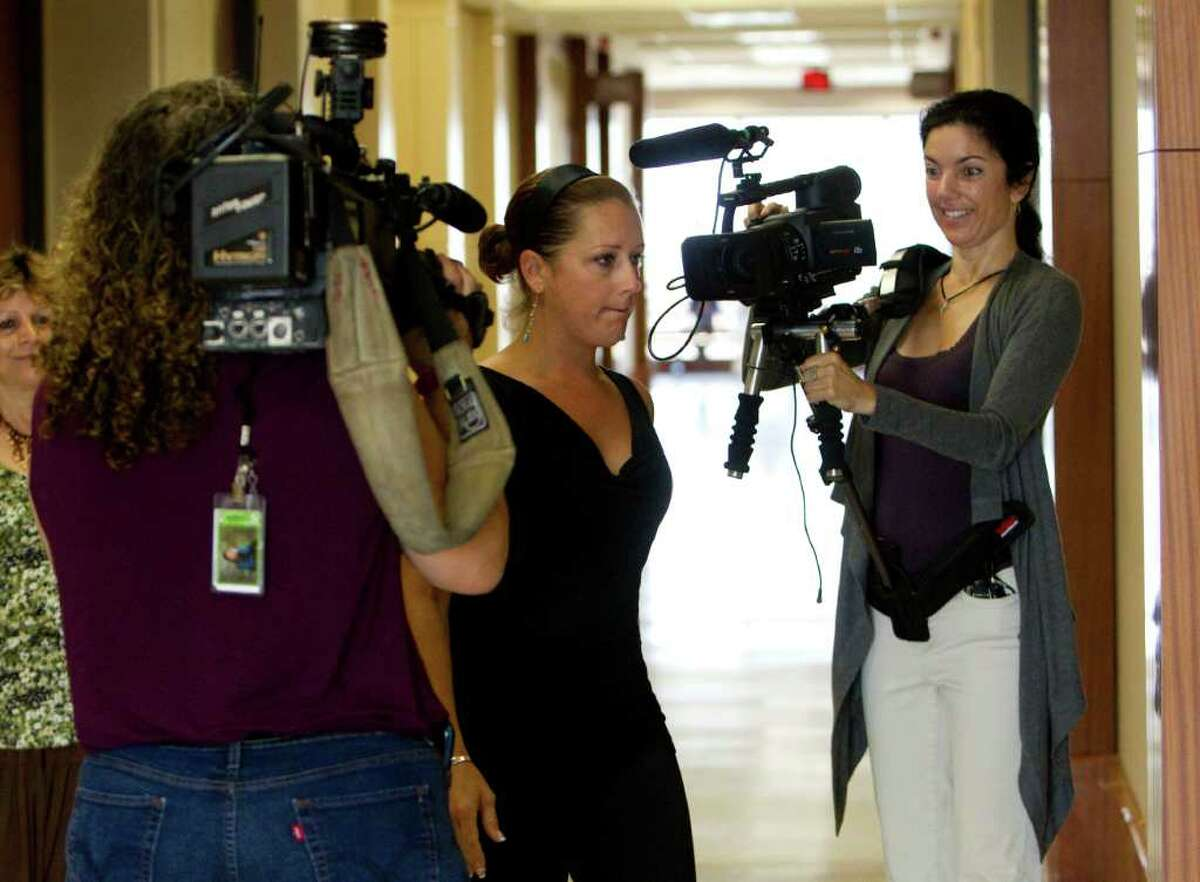 Nikki Araguz, the transgendered widow of a Wharton firefighter who died last year, walks into the Harris County Criminal Justice Center while being filmed by documentary filmmaker Cressandra Thibodeaux right before a court hearing Tuesday, June 28, 2011, in Houston. Thibodeaux is currently working on a video documentary story on Araguz. The 35-year-old is accused of stealing a Rolex watch from a woman at a bar on Feb. 24. Araguz was admonished by judge Vanessa Velasquez after the court found out Araguz had been seen in public drinking which goes against the rules of her bond. Thomas Araguz died fighting a fire at an egg farm on July 4. ( Johnny Hanson / Houston Chronicle )