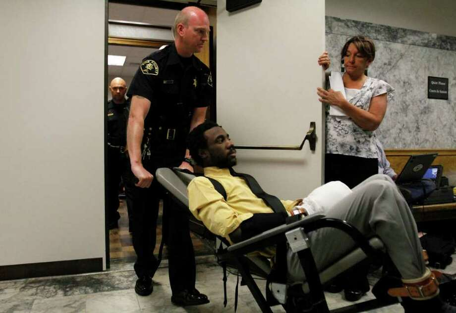 Accused killer Isaiah Kalebu is surrounded by security and press as he is wheeled from court on Wednesday, June 29, 2011 at the King County Courthouse in Seattle. Kalebu is charged with killing Teresa Butz in her South Park home in 2009. Photo: JOE DYER / SEATTLEPI.COM