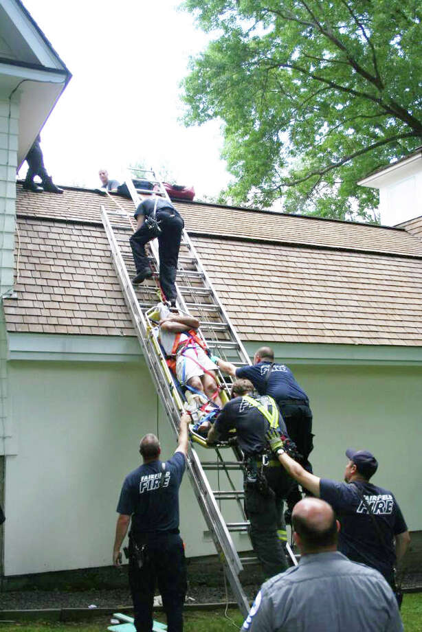 Fairfield firefighters successfully rescued Wednesday a man who had fallen from an upper roof of a Mill Hill Road home onto a lower section of the home. The man apparently fractured his right leg. Photo: Contributed Photo / Fairfield Citizen contributed