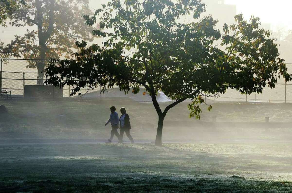 Two walkers round the track in the morning fog at Scalzi Park in Stamford, Conn. on Thursday October 28, 2010.