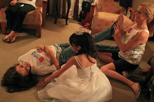 metro - Miss San Antonio Domonique Ramirez gets a foot massage from family friend Kim Thompson while Ramirez's cousin, Roslynn Briseno, 10, watches as they relax at the hotel in Arlington after the first night of the preliminary competition of the Miss Texas Pageant in the early morning hours of Wednesday, June 29, 2011. Briseno is in the pageant as one of Ramirez's Lone Star Princesses. LISA KRANTZ/lkrantz@express-news.net Photo: LISA KRANTZ, SAN ANTONIO EXPRESS-NEWS / SAN ANTONIO EXPRESS-NEWS