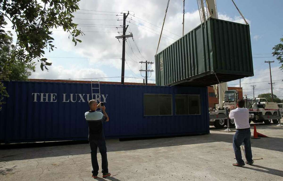 Restuarant owner Andrew Weissman (left) takes pictures Was consultant Frank Pakuszewski (right) guides a container into place that a crane lifted from the ground. Weismann is starting a restaurant called The Luxury at Avenue B and Jones that will use the freight containers as buildings and incorporate extensive landscaping and covered areas for customers to enjoy.