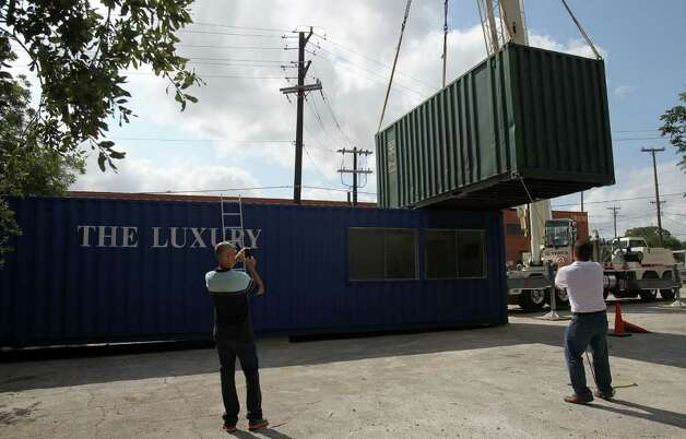 Restuarant owner Andrew Weissman (left) takes pictures Was consultant Frank Pakuszewski (right) guides a container into place that a crane lifted from the ground. Weismann is starting a restaurant called The Luxury at Avenue B and Jones that will use the freight containers as buildings and incorporate extensive landscaping and covered areas for customers to enjoy. Photo: JOHN DAVENPORT/jdavenport@express-news.net, SAN ANTONIO EXPRESS-NEWS