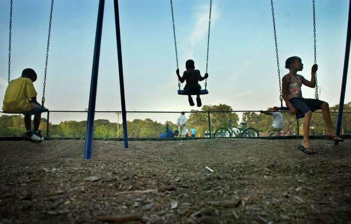 Jordan Gill, 10, Tyler Gill, 7, and their sister Brianna Gill, 11, play on the swings at Scalzi Park early one evening.
