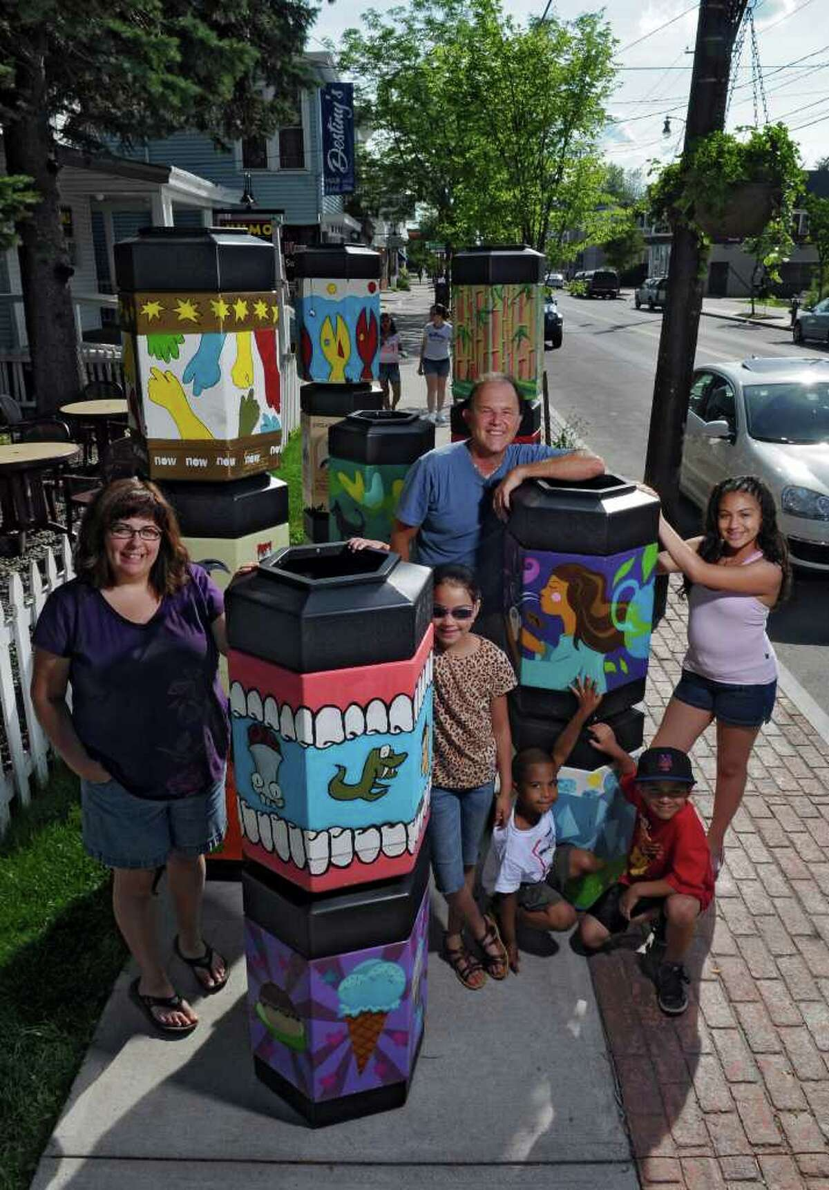 Amy Riddell, owner of Emack & Bolio's, left, and Keith Pickard, co owner of the Spectrum 8 Theatres and the Ultraviolet Cafe, center, stand near 20 new garbage cans painted by artists and commissioned by the Delaware Avenue Merchants Group that will be placed on the avenue later this week, on Monday June 28, 2011 in Albany, NY. Joining Amy and Keith are Yesenia Rios, 9, left, her brother Noel Molina, 5, left in white shirt, and their cousins Tony Stella, 7, lower right, and his sister Naomi Stella, 11, all of Albany and who live nearby. They were walking by at the time of the photograph.( Philip Kamrass / Times Union)