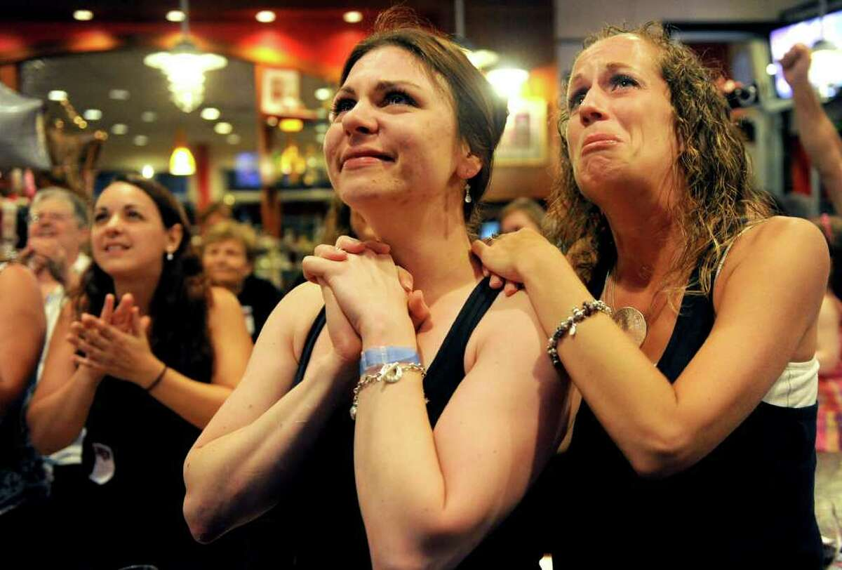"""Jessica Mullaly, right, cries as she stands with Dana Bossio and watches as Stratford-native Javier Colon is announced the winner of the show """"The Voice"""" on Wednesday, June 29, 2011."""